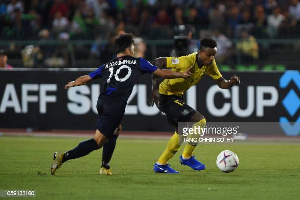 Cambodia's midfielder Kouch Sokumpheak fights for the ball with Malaysia's midfielder Mohamadou Sumareh during the AFF Suzuki Cup 2018 football match...