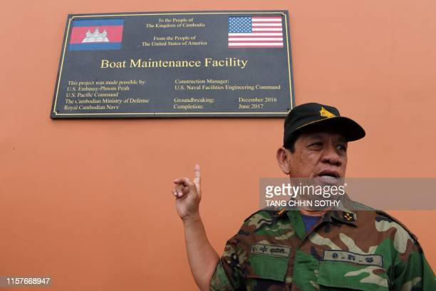 Cambodia's Ministry of Defense spokesperson Chhun Socheat shows a sign donated by the US during a government organised media tour to the Ream naval...