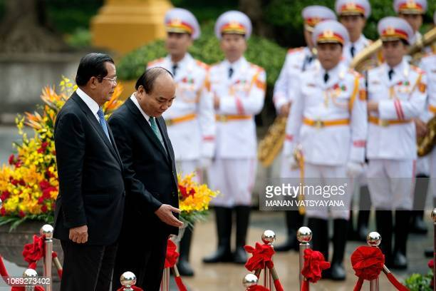 Cambodias Prime Minister Hun Sen inspects a ceremonial guard of honour with Vietnamese counterpart Nguyen Xuan Phuc during a welcoming ceremony at...