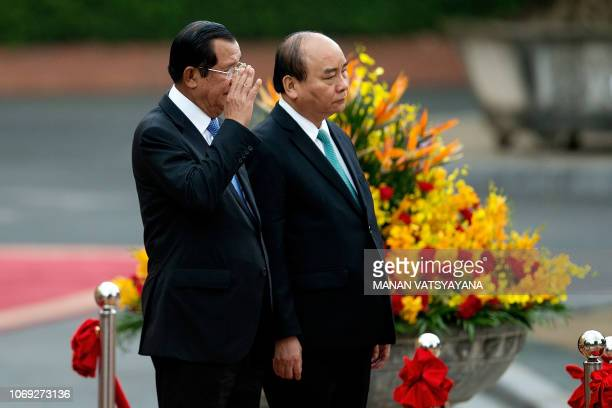 Cambodias Prime Minister Hun Sen waves after inspecting a ceremonial guard of honour with Vietnamese counterpart Nguyen Xuan Phuc at the Presidential...