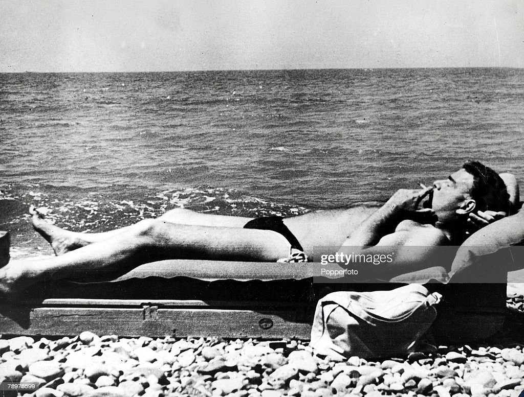 Cambridge educated Russian Spy Guy Burgess, associated with a group of Cambridge Univerty spies including Donald MacLean, Kim Philby, John Cairncross and Anthony Blunt, pictured smoking a cigarette as he relaxes on a sun lounger on the beach of the Black  : News Photo