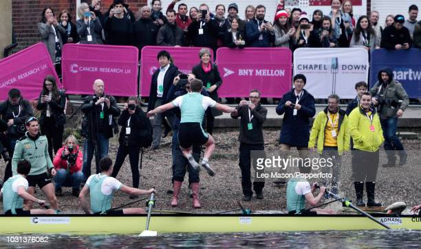 Cambridge men's crew celebrate winning at the finish after the University Men's Boat Race between Oxford and Cambridge on the River Thames between...