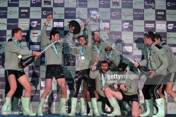 Cambridge rowers celebrate victory with champagne after finishing ahead of the Oxford boat to win the annual men's boat race between Oxford...