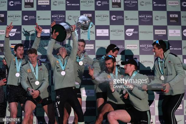 Cambridge rowers celebrate victory with the trophy and champagne after finishing ahead of the Oxford boat to win the annual men's boat race between...