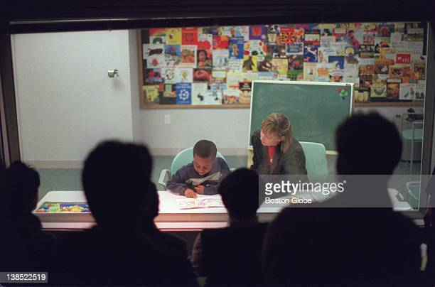 Cambridge teacher Barbara Van Sickle reads with first grader Edward Merancien while other teachers watch from behind a oneway mirror during a Reading...