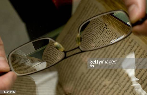 Cambridge University Library exhibitions officer John Wells poses with his glasses with the second oldest surviving copy of The Ecclesiastical...