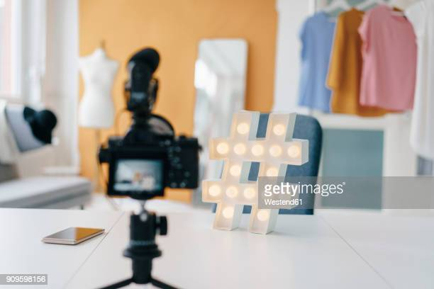 Camcorder recording hashtag sign on table in fashion studio