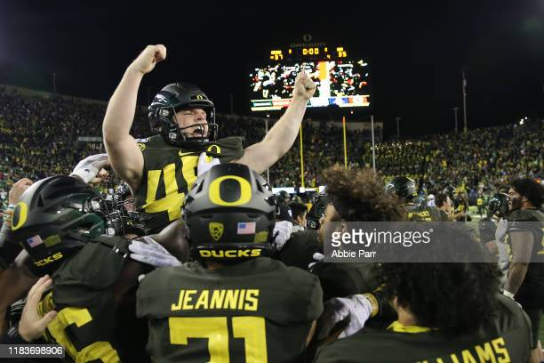 Camden Lewis of the Oregon Ducks celebrates with teammates after kicking the game winning field goal to defeat the Washington State Cougars 37-35...
