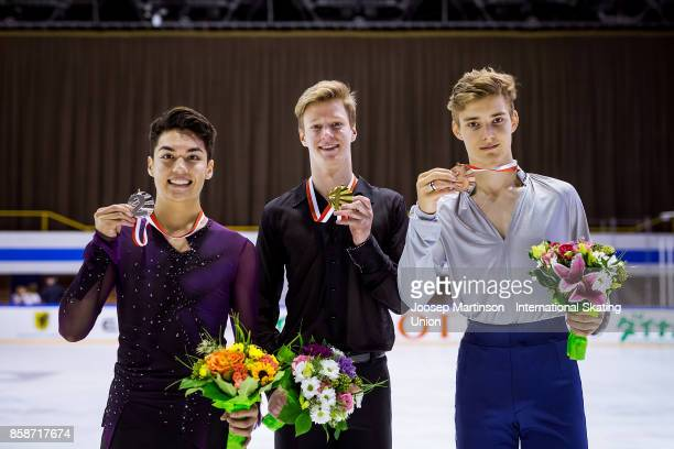 Camden Pulkinen of the United States Alexey Erokhov of Russia and Conrad Orzel of Canada pose in the Men's medal ceremony during day three of the ISU...