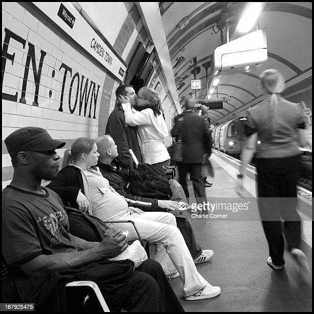 "Camden Town tube station. A girl kisses her ""boyfriend"" while he eyes up another girl on the platform. Another passenger looks on."