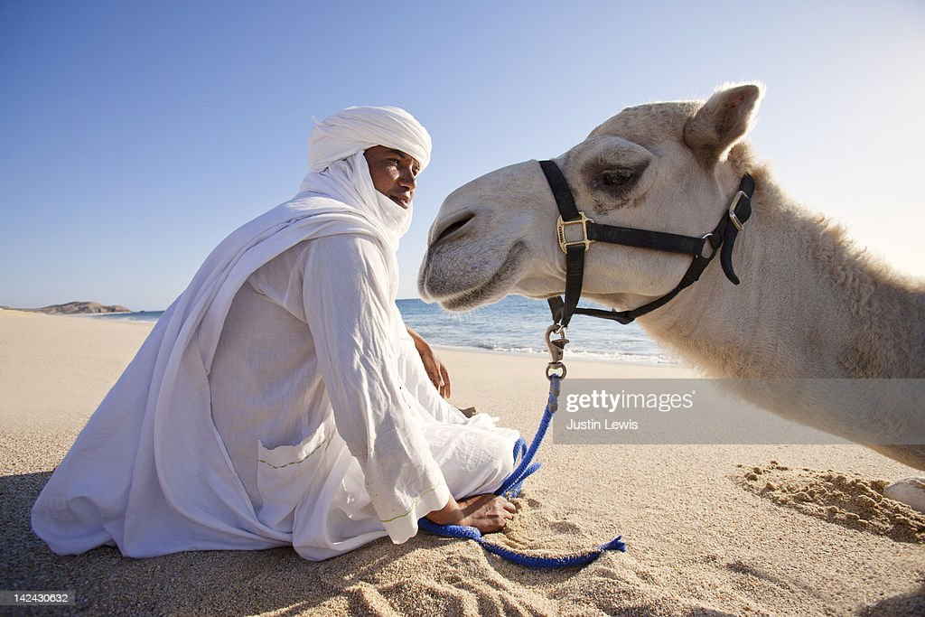 Camel and guide sitting on sandy beach in sun : Stock Photo
