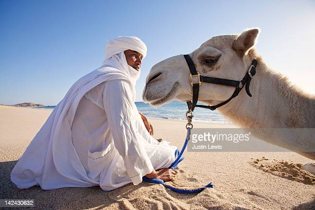 Camel and guide sitting on sandy beach in sun