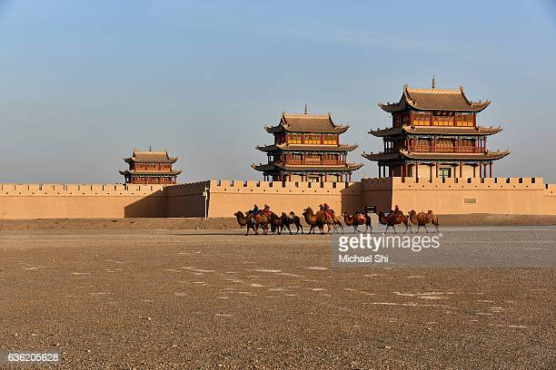 A camel caravan passing by Fort Jiayuguan,  the Western Terminus of the Great Wall of China, standing in the middle of the Gobi Desert.