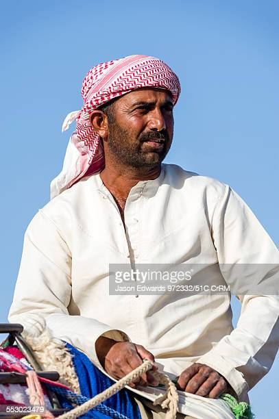 Camel herder leads his racing camels across a desert plain on their way to a race carnival. Al Wasil, Sharqiya Region, Sultanate of Oman.