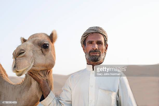 camel herder with camels at camel farm - arab old man stock pictures, royalty-free photos & images
