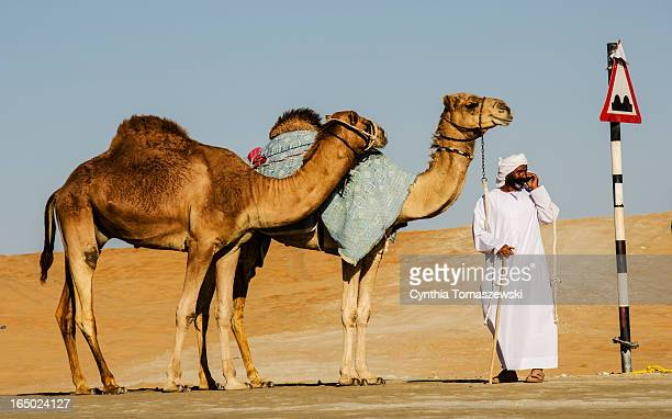 Camel owner or herder placing a cell phone call while waiting with his camels near a speed hump. A great mix of traditional and modern.