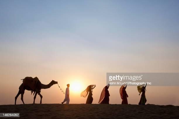 camelo andar atrás de mulheres e homem indiano - rajastão imagens e fotografias de stock