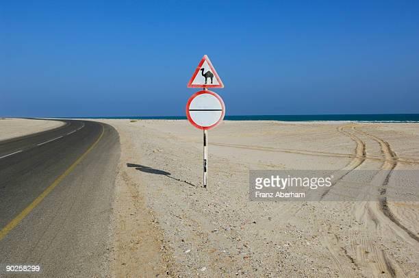 Camel warning sign by desert road , Al-Sharqiyah , Oman