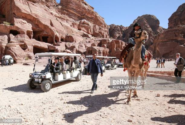 A cameleer passes by a convoy of carts transporting King Harald V of Norway and his wife Queen Sonja during their visit to Jordan's archaeological...