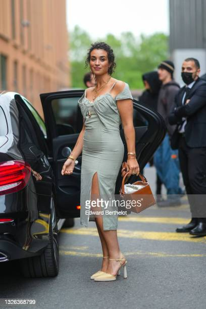 Camelia Jordana wears a pale green slit dress, a brown square-shaped / cube-shaped Jacquemus leather bag, high heels pointed pale yellow sandals,...