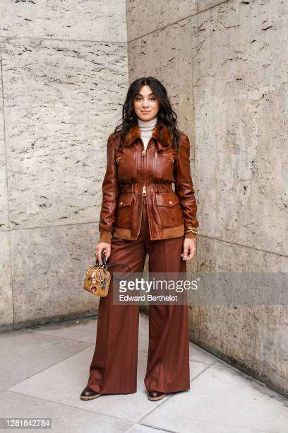 Camelia Jordana wears a white wool turtleneck pullover, a brown leather jacket, brown flared pants, a brown Chloe bag, outside Chloe, during Paris...