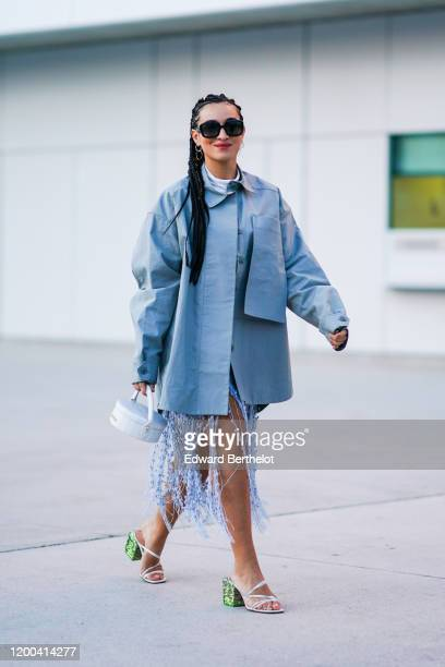 Camelia Jordana wears sunglasses a blue oversized jacket a white circular bag shoes with green heels a fringed skirt outside Jacquemus during Paris...