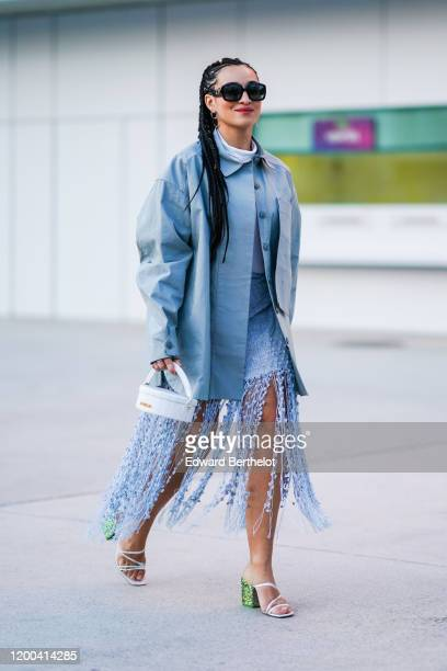 Camelia Jordana wears sunglasses, a blue oversized jacket, a white circular bag, shoes with green heels, a fringed skirt, outside Jacquemus, during...