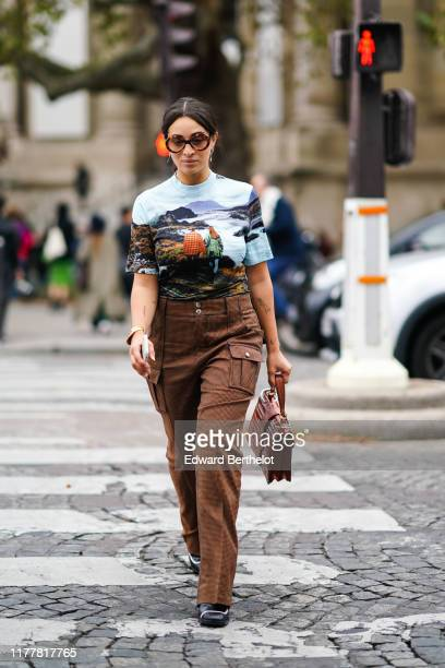Camelia Jordana wears sunglasses earrings a bracelet a Chloe top with a landscape print brown houndstooth cargo pants a brown crocodile Chloe handbag...