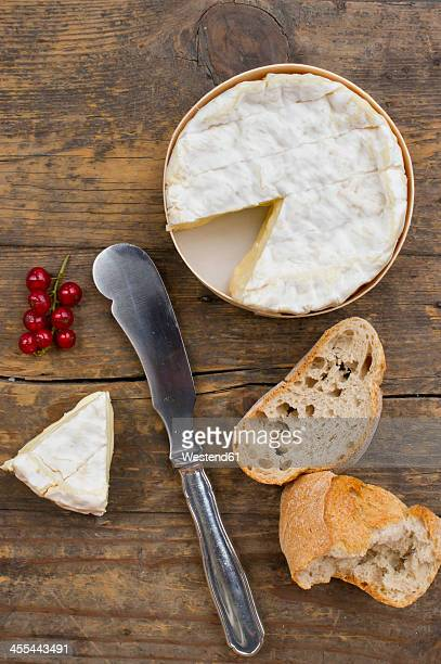 camember cheese with red currant and baguette on wooden table - camembert stock photos and pictures