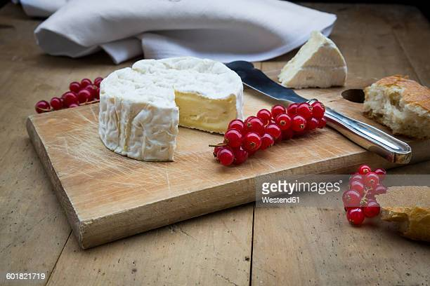 Camembert, bread and red currants on wood