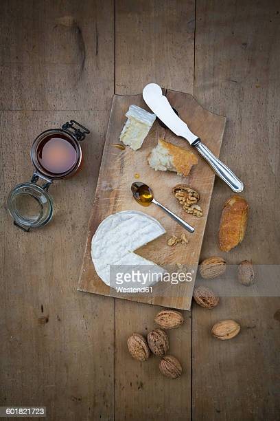 Camembert, bread, walnuts and glass of honey on wood