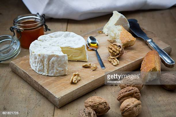 Camembert, bread, walnuts and honey on wood