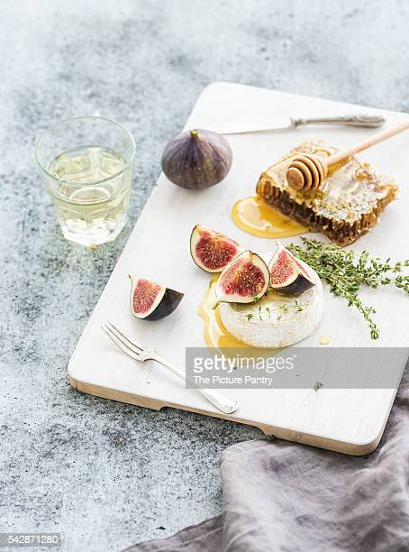 Camembert or brie cheese with fresh figs, honeycomb and glass of white wine on serving board over grunge rustic grey backdrop