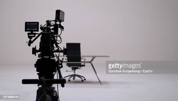 camera against table and chair over white background - film studio stock pictures, royalty-free photos & images