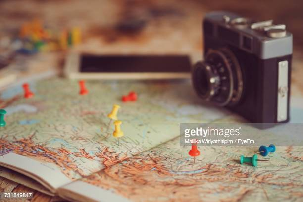 Camera And Mobile Phone With Colorful Thumbtacks On Map