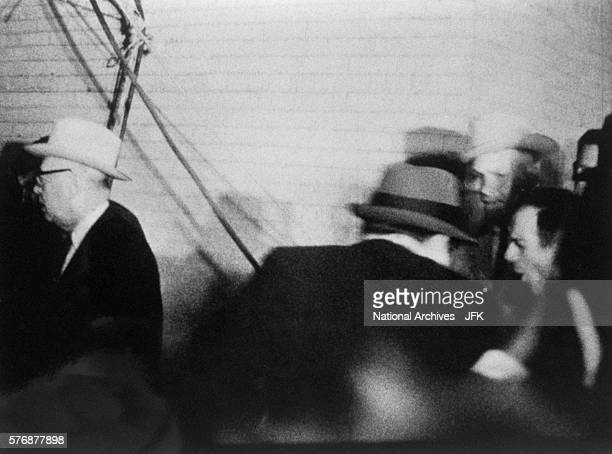 A camera captures the back of Jack Ruby as he shoots Lee Harvey Oswald who is being escorted by guards during a television press conference at the...