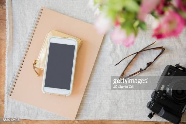 Camera, cell phone, purse, notebook and wallet on table