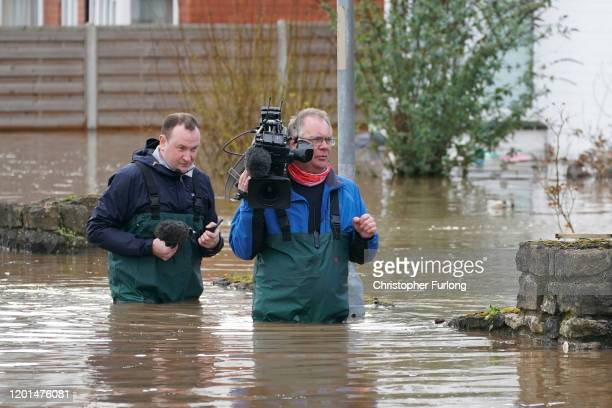 Camera crew wade through the flooded waters after the River Wye burst its banks following Storm Dennis on February 17, 2020 in Hereford, England....