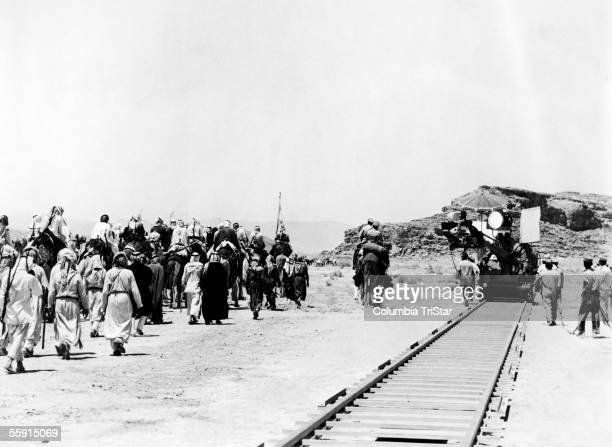 A camera crew with camera crane mounted on railway track films a scene of actors walking and riding camels through the sand on the set of the film...