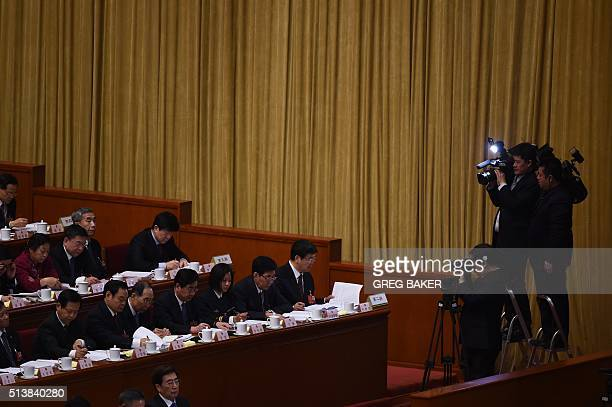 Camera crews film delegates during the opening session of the National People's Congress in the Great Hall of the People in Beijing on March 5 2016...