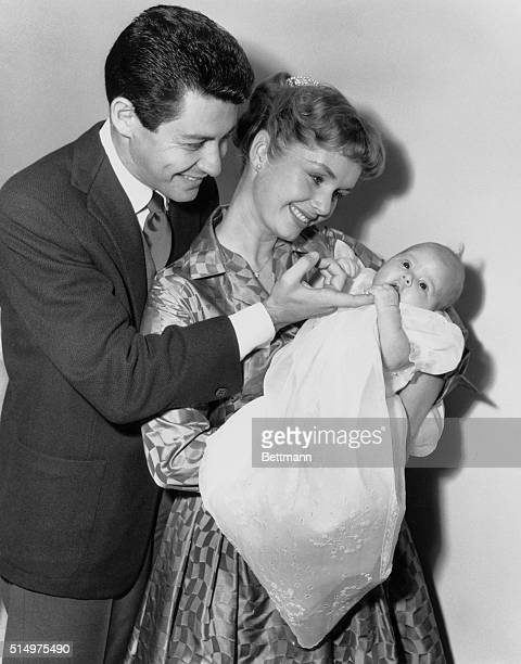 Camera Debut. Hollywood, California, USA: Eddie Fisher and wife, Debbie Reynolds, gaze proudly at their baby daugher, Carrie Frances Fisher, here...