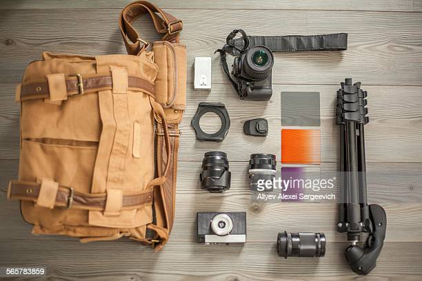 Camera equipment and camera bag arranged on table, overhead view