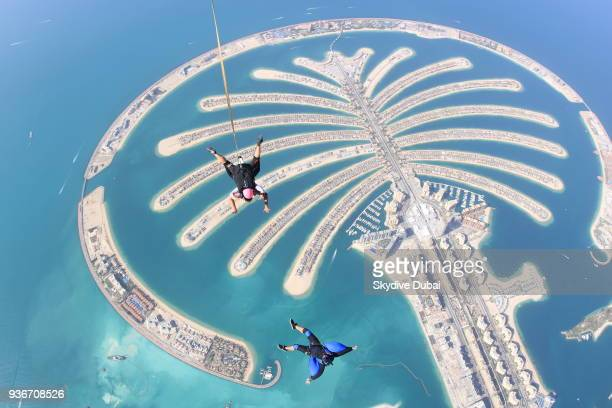 A camera flyer captures a tandem skydive over the man made island the Palm Jumeirah Island on March 1 2018 in Dubai United Arab Emirates