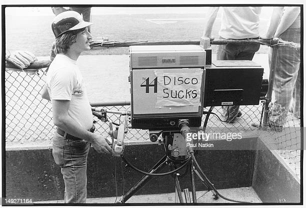 A camera for Chicagoarea television station 44 carries a sign that reads 'Disco Sucks' during an antidisco promotion at Comiskey Park Chicago...