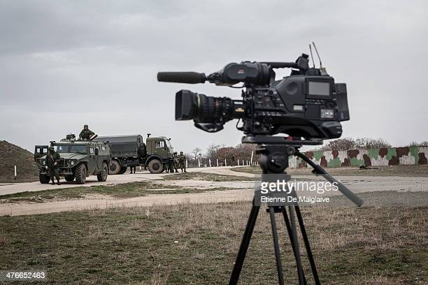 A camera from a media crew stands next to a roadblock manned by soldiers under Russian command at Belbek Airfield after unarmed Ukrainian troops...