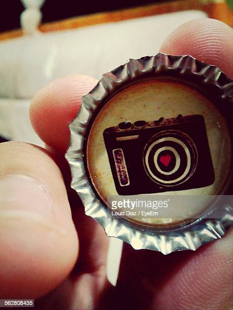 Camera Icon On Bottle Cap Held By Person
