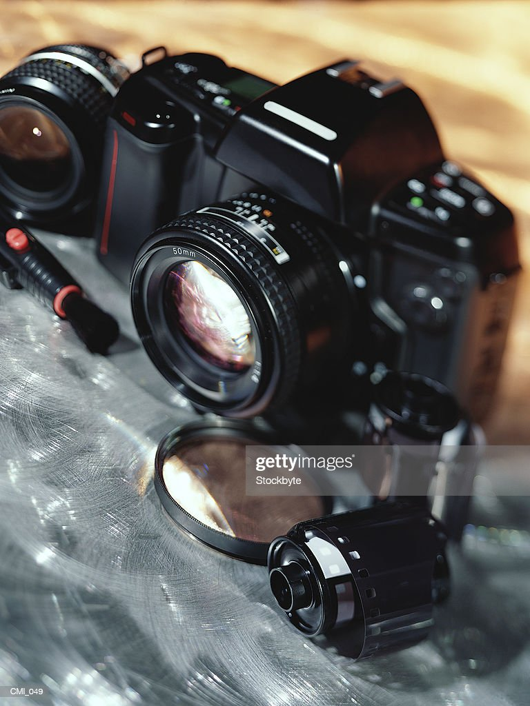 Camera, lenses, and film canister : Stock Photo