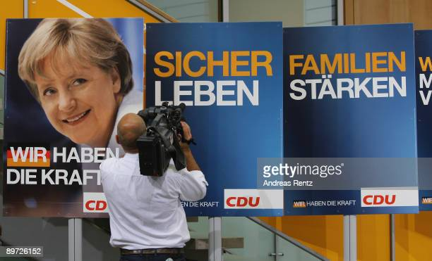 A camera man films a placard during the presentation of the CDU election campaign billboards on August 10 2009 in Berlin Germany German Chancellor...