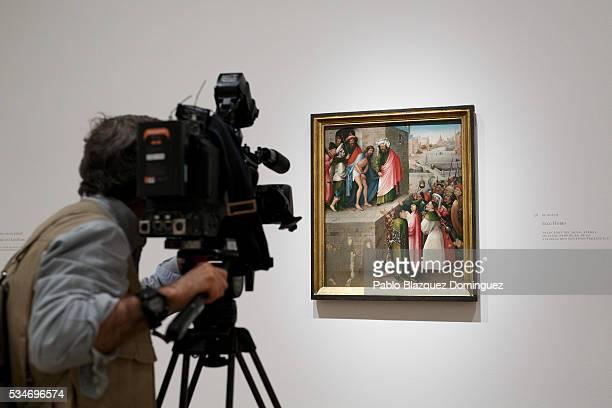 A camera man films 'Ecce Homo' by Dutch painter Hieronymus Bosch during a press preview of the 'El Bosco' 5th Centenary Anniversary Exhibition at El...