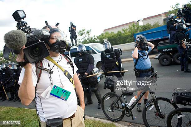 A camera man protects himself against tear gas during a stand off between heavily armed Minneapolis police officers and demonstrator near the Xcel...